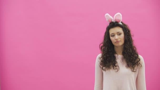 Junge kreative paar auf rosa Hintergrund. Mit abgedroschenen Ohren auf dem Kopf. Während dieser Mann gibt dekorative bunte Eier an die Ehefrau. Sanft zu küssen, zusammen in die Kamera schaut. Ostern-Konzept