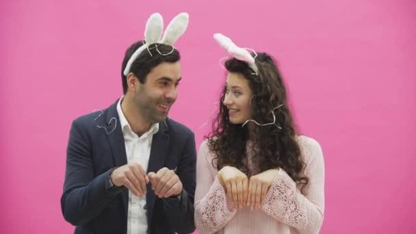 Junges sexy Paar auf rosa Hintergrund. Mit abgedroschenen Ohren auf dem Kopf. Während dieser Reproduktion sexuelle Kaninchen Bewegungen und sieht nach einer Weile gehen Sie, aus dem Rahmen.