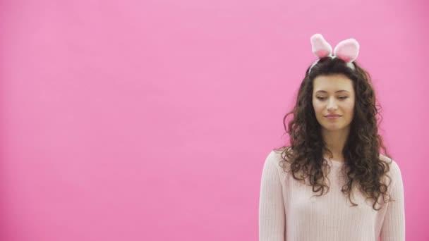 Junge schöne Paar stehend auf einem rosa Hintergrund. Mit abgedroschenen Ohren auf dem Kopf. Während dieser Mann gibt seine Frau einen Korb mit bunten Eiern.