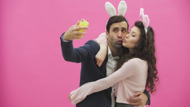 Young tender pair standing on a pink background. Looking at the phone while doing selfie on the mobile phone with the ears of a pink rabbit on the head. Happy family is preparing for Easter