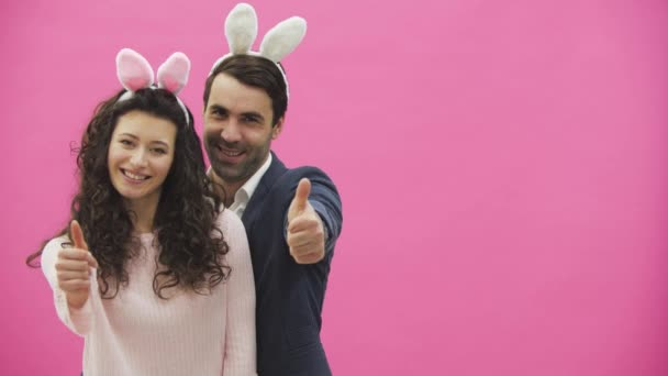 Young couple standing on a pink background. During this, the gesture class shows a smile, looking at the camera. Happy family is preparing for Easter, with the ears of a pink rabbit on its head.