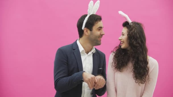 Beautiful young couple standing on pink background. At the same time, they smile to recreate the movements of hares after kissing. Together with the pink paws on the head. Happy family is preparing