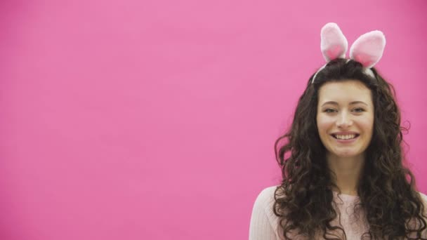 The young girl stands on a pink background. She approaches a man and gives decorative multicolored eggs. During this he kisses her. Sincerely smile.