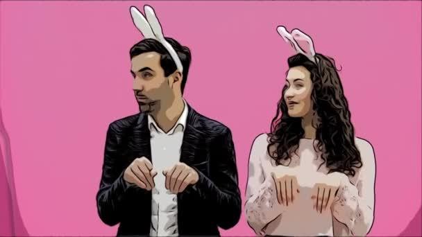 Junges Paar stehend stehend auf rosa Hintergrund. Während dieser Zeit sind sie in Gesindel Ohren gekleidet. Mit Blick auf einander, sprechen und Lächeln. Ostern-Konzept.