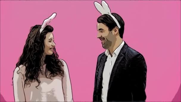 Junges Paar sind schön auf rosa Hintergrund. Während dieser Zeit sind sie in Gesindel Ohren gekleidet. Blick auf einander, spielen sie Karotten, zeigen verschiedene Kaninchen Bewegungen. Ostern-Konzept.
