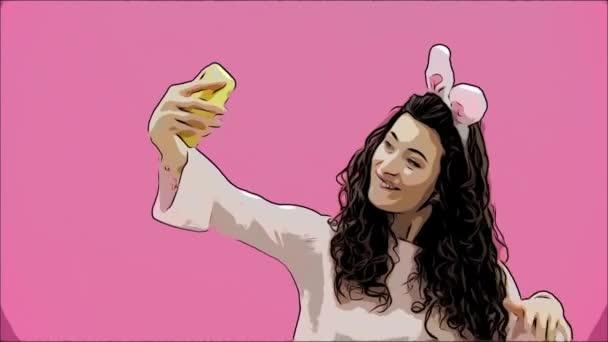 schöne junge Mädchen steht auf einem rosa Hintergrund. Dabei gibt es Hasenohren auf dem Kopf. macht ein Foto von Sephi am Telefon, das die Zunge zeigt. Ostern.