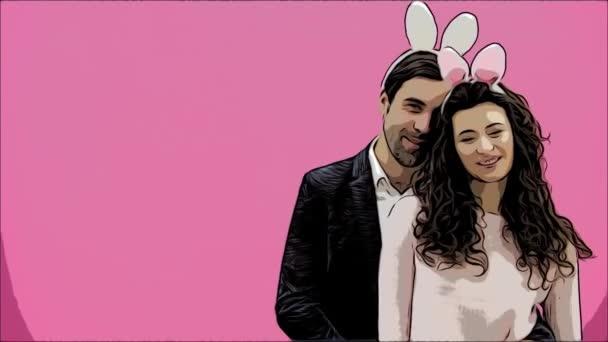 junges kreatives Paar auf rosa Hintergrund. mit abgedroschenen Ohren auf dem Kopf. Dabei zeigen zwei die Gesten der Klasse und schauen sich gemeinsam an. Osterkonzept.