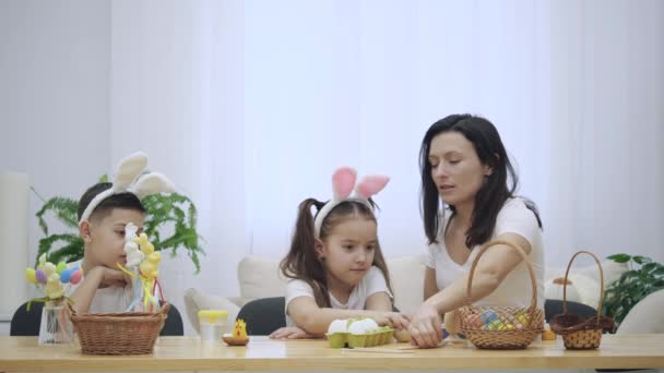 Mother is with her kids: daughter and son, who are wearing bunny ears, sitting at the holiday table with a basket, white and yellow rabbits. Slow Motion