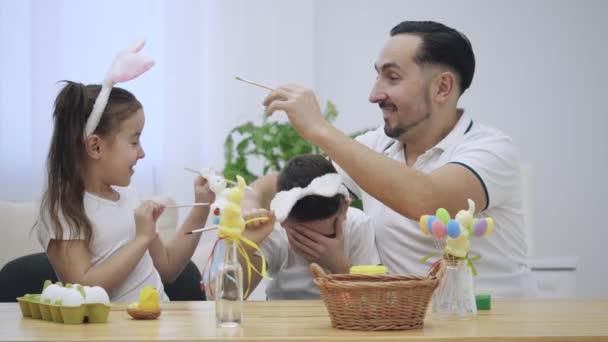 Otec je s jeho děti: dceru a syna, kteří jsou na sobě uši zajíček, sedí u stolu holiday a drží ve svých rukou štětce. Členové rodiny se snaží malovat obličeje každého z nich. Pomalu