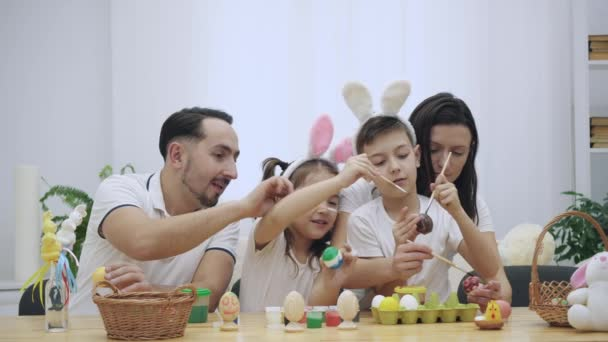 Parents with their adorable and cute kids, who are really similar to them, are colourizing Easter eggs, sitting at the wooden table, full of Easter decorations.