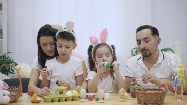 Parents with their adorable and cute kids, who are really similar to them, are colourizing Easter eggs, sitting at the wooden table, full of Easter decorations. Family is concentrated on the activity.