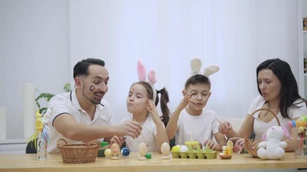 Szülők a Cser és aranyos gyerekek, akik tényleg hasonló őket, van colourizing húsvéti tojás, ül a fából készült asztal, tele a húsvéti dekoráció. Lánya fest egy bajusz a atyák