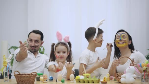 Parents with their brisk and little kids, are colourizing each other, sitting at the wooden table, full of Easter decorations. Family kindly invites to spend fun time with them showing a gesture