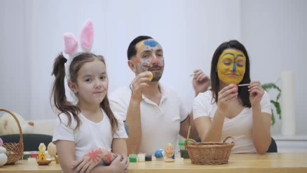 Cute couple is colorizing each other with a help of Easter paint-brush. Their daughter says: Shame on you I have grown up, but neither you . Childish couple came back to childhood.