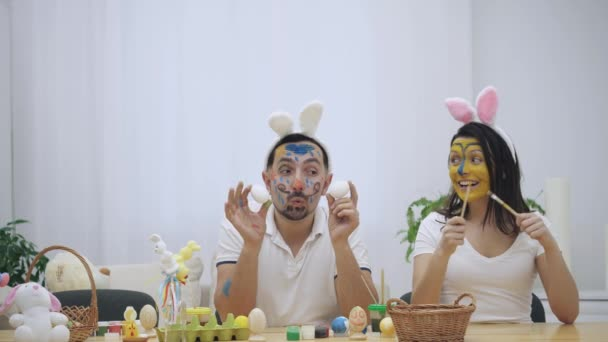 Cute and adorable couple came back to childhood. Man is holding two eggs in his hands and a woman is holding two paint-brushes in her. Couple wearing bunny ears. Slow motion video.
