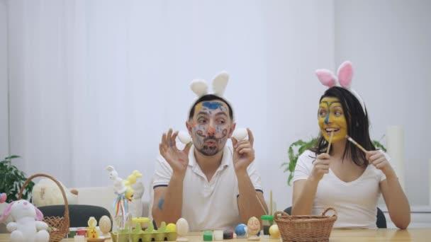 Roztomilé a roztomilý pár se vrátil do dětství. Muž drží v ruce dvě vejce a žena je v ní drží dva štětce. Několik na sobě uši. Zpomalené video.