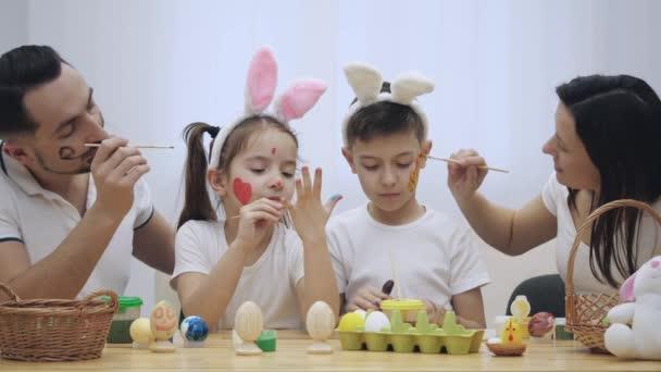 Rodiče se svými dětmi Denis a roztomilé jsou colourizing navzájem, sedící u stolu, plné velikonočních dekorací. Otec je Malování červené srdce dcery tváře, matka je Malování