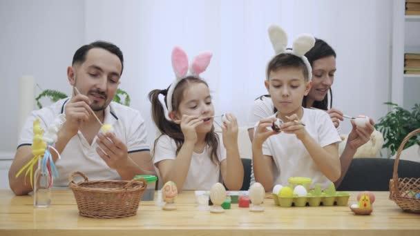 Rodiče s dětmi roztomilé a roztomilý, kteří jsou pro ně opravdu podobné, jsou colourizing kraslic, sedící u stolu, plné velikonočních dekorací. Rodina se soustředí na činnost