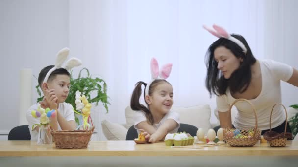 Mother is with her kids: daughter and son, who are wearing bunny ears, sitting at the holiday table with a basket, white and yellow rabbits. Girl is playing with Easter chicken. Slow Motion