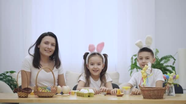 Mother is with her kids: daughter and son, who are wearing bunny ears and touching them, laughing sincerely, sitting at the holiday table with a basket, white and yellow rabbits and some other Easter