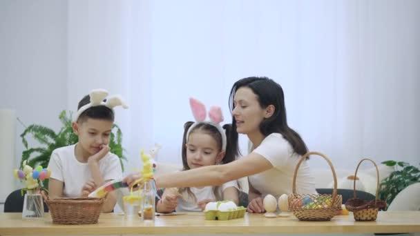 Anya van vele a gyerekek: lánya és fia, aki visel nyuszi füle ül az ünnepi asztalra teljes húsvéti dekorációk. Anyu ad neki a gyermekek különböző színű festék.