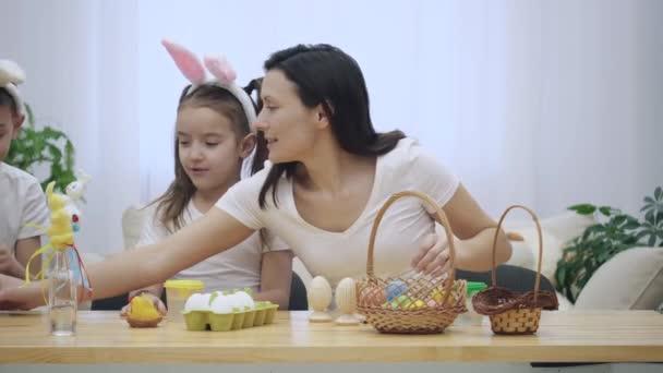 Matka je s její děti: dceru a syna, kteří jsou na sobě uši zajíček, sedící u stolu dovolená s velikonoční ozdoby. Maminka se připravuje nástroje pro řemesla.