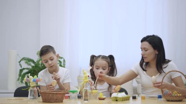 Anya van vele a gyerekek: lánya és fia, aki ül az ünnepi asztalra húsvéti dekorációk. Család az koncentrált, és így a vízi jármű, színezéssel húsvéti tojás. Hirtelen, apa jön és