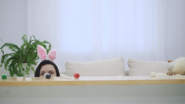 Childish mother and her son with bunny ears on their heads are hiding under the wooden table, full of Easter decorations. They are looking out of the table with cheerfull face expression. Game hide