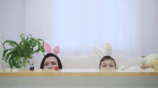 Happy mother and her son with bunny ears on their heads are hiding under the wooden table, full of Easter decorations. They are looking out of the table with cheerfull face expression. Game hide and