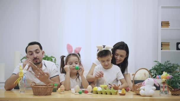 Parents with their adorable and cute kids, who are really similar to them, are colourizing Easter eggs, sitting at the wooden table, full of Easter decorations. Family is concentrated on the activity