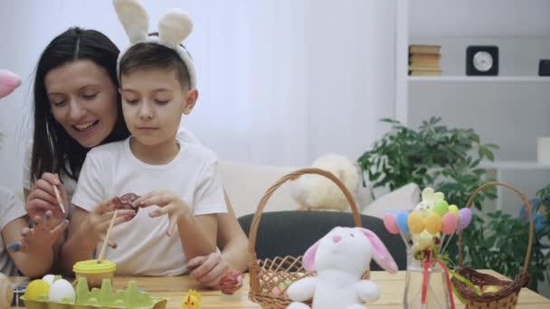 Aranyos kisfiú bunnys füle anyák térdre ül, és azt mutatja, a festett körmök. Anya festészet lányai piros festéket ecsettel szegek.