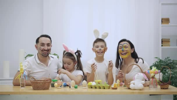 Rodiče s dětmi svižným a malé mají re-colourized navzájem, sedící u stolu, plné velikonočních dekorací. Rodinné laskavě vlna, ukazující gesto. Velikonoční koncept. No tak