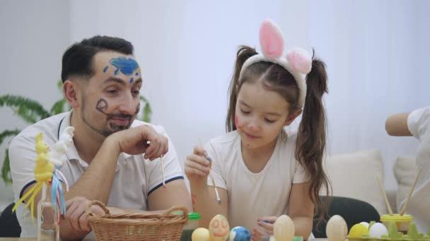 Rozkošná holčička s uši zajíček je kolorování její tvář otce. Maluje modrý mrak s kapkami. A tatínek cítí malbu a začne napodobovat, pláč.