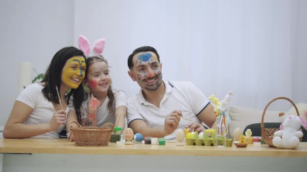 amily is sitting at the table, full of Easter decorations and showing different emotions. From happiness to sadnes. Shift of emotions.