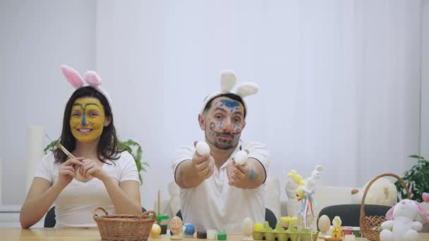 Cute and adorable couple came back to childhood. Man is holding two eggs in his hands and a woman is holding two paint-brushes in her. Couple wearing bunny ears. They are raising their thumb fingers