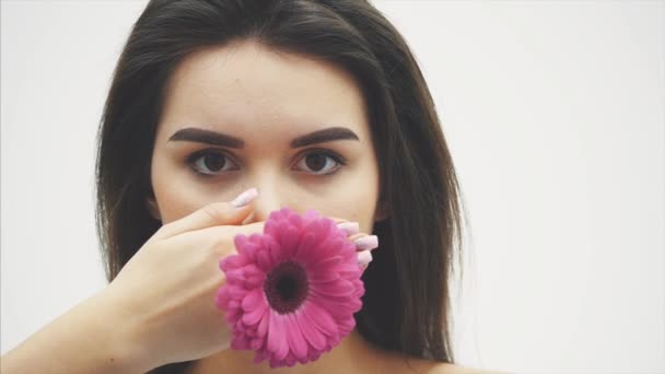 Young attractive lady close-up on white background. Keeping the flower in hand raises it at the level of the face. Isolated brunette spa nude makeup.