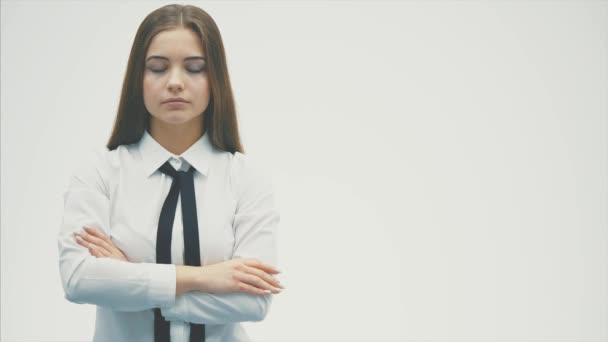 Fiatal csinos üzleti lány állt a fehér háttér. Ez alatt, úgy néz ki a kamerát helyezve a kezét a zsebébe.