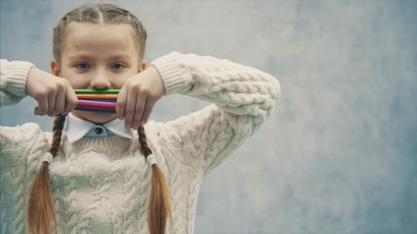 Funny emotional pupil is hiding her face behind a stack of colorful pencils.