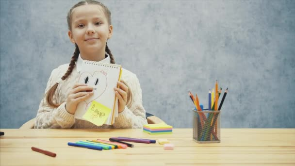 Schulkind zeigt ihr Bild eines lächelnden Herzens, zwinkert und zeigt ihre Zunge.