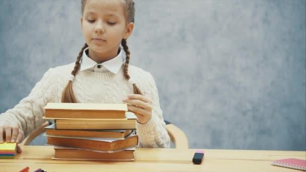 Nettes Schulmädchen umarmt einen Stapel Bücher.