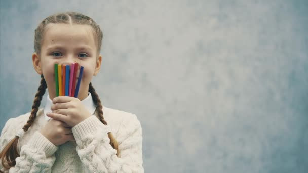 Funny emotional schoolgirl is hiding her face behind colored pencils.