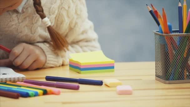 Školka obklopená wirh uměleckými potřebami je soustředěna na kreslení.