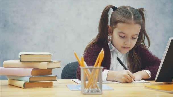 Értelmes iskoláslány előad lecke rövid idő ülő-nél asztal. Ez alatt az írás, a ceruza vesz egy sárga színű.