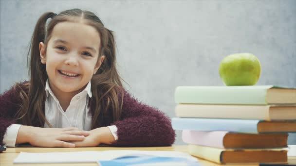 intelligentes Schulmädchen, am Tisch sitzend. Während dieser Zeit wird ein Aufkleber auf einem gelben Blatt aufbewahrt. hat einen traurigen Blick.