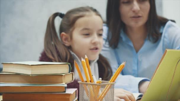 Matka, zatímco dělá domácí práce u stolu doma v učení problémy domácí viditelně frustrováni s dcerou.