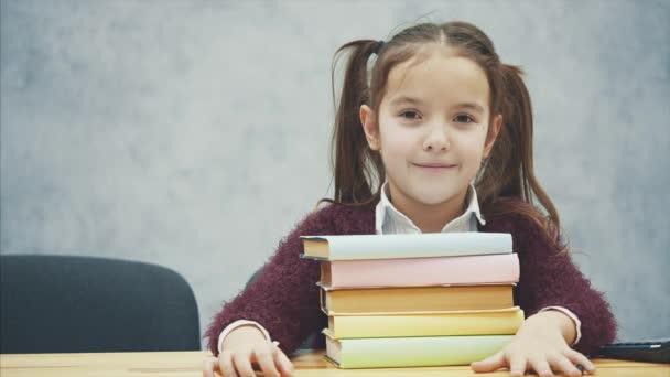 U stolu sedí školka. Během tohoto tance se dívá na kameru a zavřela oči. Když si osvojil hromádku knih, zvedl hlavu.