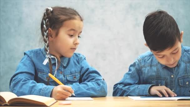 Studenti, bratr a sestra, sedí u stolu, píše, pak bojují za vládce.