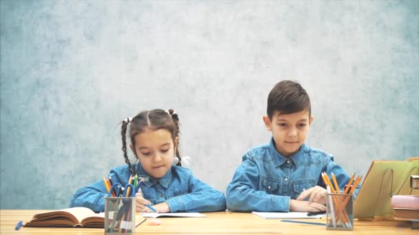 Schoolkids, testvér, ül az asztalnál, írásban. Akkor mutatva ujjaikat megjelöl mint ha ők jött megjelöl-val egy kitűnő eszme.
