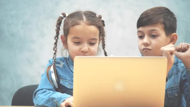 Cute little schoolkids sitting at the desk with the laptop, listening to the music, dancing.