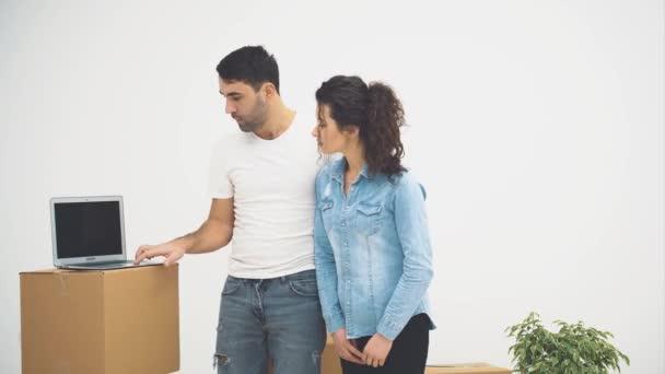 A fiatal pár együtt költözött egy új lakásba. Megvitatnak néhány részletet. A pár körülnéz. Másold a helyet. Felvétel, animáció. 4k.